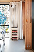 Stack of wooden crates in front of floor-length pale curtain next to stained glass window