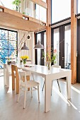 White dining table and various chair in open-plan interior below wooden gallery