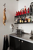 Black kitchen with shelves, retro toaster and ham hanging from butchers' hook