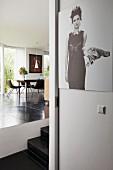 Blick auf Essbereich im Designerstil mit glänzendem schwarzem Fliesenboden und Frauenportrait