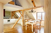 Open-plan kitchen and dining area in converted attic with rustic wooden roof beams