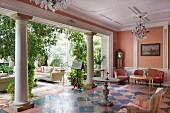 Salon mit Fliesenboden im Schachbrettmuster und Säulenreihe, vor Wintergarten mit Grünpflanzen