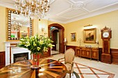 Vase of lilies on round wooden marquetry table in luxurious dining room