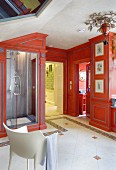 White armchair in luxurious bathroom with red-painted custom fitted cabinets and shower cubicle to one side