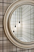 Bulb lamps reflected in round mirror on wall