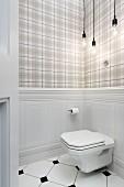 Toilet mounted on wainscoting below Bulb lamps against tartan wallpaper