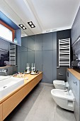 Elongated modern bathroom with long washstand below mirrored wall opposite toilet and bidet