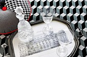 Glasses and crystal carafe on tray on bedspread with op-art graphic pattern