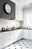 Antique station clock on black extractor hood housing in white, elegant, country-style fitted kitchen