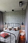 Black vintage metal bed flanked by pendant lamps against tiled wall with black and white floral pattern in bedroom
