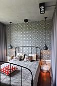 Schwarzes Vintage Metallbett zwischen Pendelleuchten vor gefliester Wand mit schwarz weißem, floralem Muster im Schlafzimmer