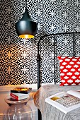 Black vintage metal bed and pendant lamps against tiled wall with black and white floral pattern in bedroom