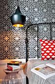 Schwarzes Metallbett mit Designer-Pendelleuchte vor schwarz-weiss gefliester Wand mit floralem Muster