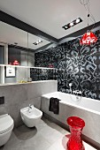 Designerbad in Grautönen mit roten Farbakzenten, 'Campari Light' Pendelleuchte vor schwarz-grau gefliester Wand mit floralem Muster