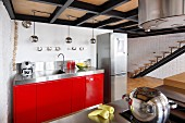Kitchen counter with red base units next to stainless steel fridge-freezer in loft apartment