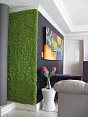 Strip of green fluffy fabric on wall next to bouquet on white side table below artwork on black wall in living room