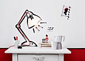 DIY light sculpture on white, vintage chest of drawers - lamp socket on red cable attached to wall inside table lamp painted on wall