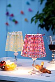 Brightly printed paper folded into concertinas as lampshades for tealights in stemmed glasses