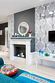 Elegant, grey and white faux fireplace and chimney breast flanked by wallpaper with pattern of stylised trees; colourful scatter cushions on blue sofa in foreground