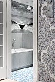 View through open door into bathroom with black and white mural wallpaper depicting sea and sky reflected in mirrors on two walls