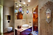 Colourful, patterned spherical lamps above washstand with pebble mosaic tiles, separate toilet and vintage Oriental-style wall design