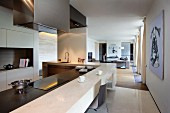 Designer kitchen with breakfast bar on L-shaped worksurface; elongated interior in natural shades in background