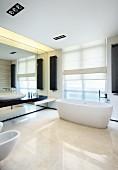 Kühles, weisses Designerbad mit dunklen Akzenten durch Wandheizkörper und die Waschtisch-Ablage an einer durchgehenden Spiegelwand