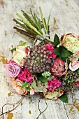 Bouquet of roses and protea on vintage wooden surface