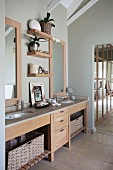 Modern, custom washstand with twin sinks in stone counter and pale wooden drawer unit in open-plan bathroom with walls painted pale grey