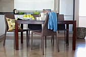 Dark wooden dining table and grey plastic chairs on polished concrete floor