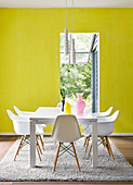 White classic chairs around modern dining table on Berber rug in front of wall painted in bright lemon yellow