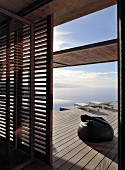 View through louvre doors onto wooden deck with beanbag, sun loungers and sea view