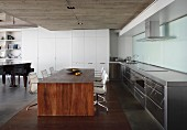Minimalist, solid-wood dining table and classic swivel chairs in open-plan kitchen with concrete ceiling