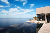 Contemporary house with encircling terrace and infinity pool with sea view