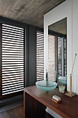Washing area with glass basin on minimalist wooden washstand and French windows with closed wooden louvres