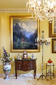 Antique, dark wood bureau below gilt-framed landscape on yellow-painted wall with chandelier floor lamp to one side