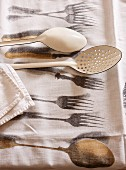 White enamel, vintage cooking utensils on table cloth printed with cutlery pattern