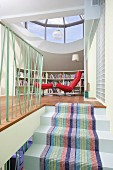 Striped stair runner on masonry staircase, open-plan attic room with red easy chair and footstool under glass dome