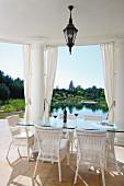 weiße Rattanstühle um Glastisch auf überdachter Terrasse, zwischen Säulen Blick in Garten mit Teich