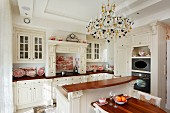 White country-house kitchen with dining area, counter and chandelier in grand interior