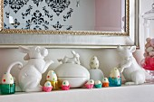 Easter arrangement on mantelpiece, white china animal figurines and painted eggs in glass and paper cases