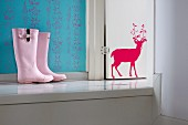 Pink child's wellingtons on platform next to white-painted wooden door with red stag motif