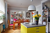 Free-standing, bright yellow counter with drawers and grey worksurface, vase of narcissus, Easter decoration hanging from pendant lamp and Biedermeier-style dining set in open-plan interior