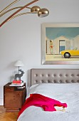 Pink dress on bed with grey upholstered headboard below framed modern artwork on wall