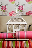 Roll of colourful wallpaper and vintage bird cage on armchair with plain grey and brightly striped covers in front of wallpapered wall