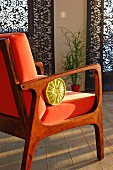Fifties-style chair with wooden frame and orange cushions in front of panel blinds with dark devoré pattern