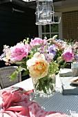 Blumenstrauss mit Pfingstrosen und Anemonen in Glasvase auf Terrassentisch