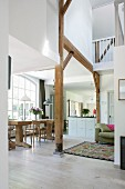 Open-plan interior with exposed wooden structure, gallery and dining area