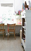 Simple wooden chairs at desk below window and horse ornaments on open-fronted, white-painted cabinet in children's bedroom