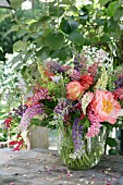 Summer bouquet of lupins, roses and gloriosa lilies in glass vase